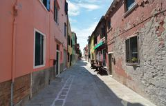 An inviting backstreet between brightly painted houses Stock Photos