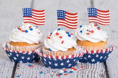 Patriotic cupcakes with sprinkles and American flags - stock photo