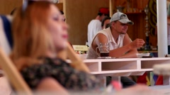 A woman looks at a man in a summer bar at the next table Stock Footage