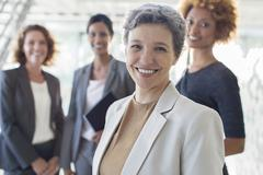 Portrait of smiling mature businesswoman with office team in background - stock photo