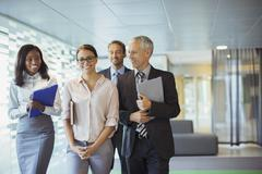 Business people walking through office building together - stock photo