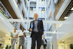 Business people walking through office building Stock Photos