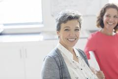 Portrait of smiling mature businesswoman with colleague in background Stock Photos