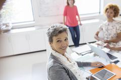 Portrait of smiling mature businesswoman at desk in office - stock photo
