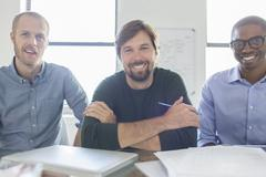 Portrait of three smiling businessmen in office Stock Photos
