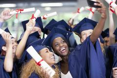 Students taking selfie after graduation ceremony - stock photo