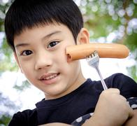 Child eating a sausage - stock photo