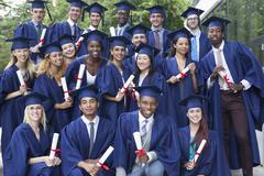 Portrait of university students in graduation gowns outdoors Kuvituskuvat