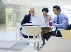 Business people gathered around laptop in office building cafe Stock Photos