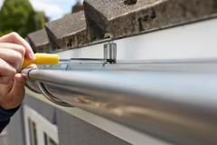 Close Up Of Man Replacing Guttering On Exterior Of House - stock photo