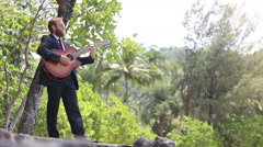 Guitarist plays standing against tropical trees Stock Footage