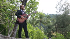 Guitarist plays and gesticulates against tropical trees Stock Footage