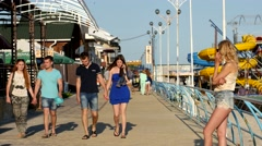 People walking along the promenade in the seaside resort at evening Stock Footage