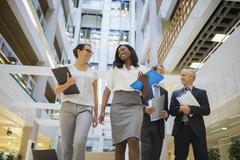 Business people walking together in office building - stock photo