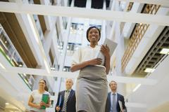Business people walking in office building - stock photo