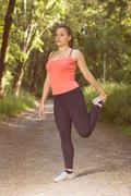 Stock Photo of Fitness Healthy Young Woman Stretching Outdoor . Portrait of caucasian brunet