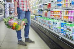 Man carrying full shopping basket in grocery store Stock Photos