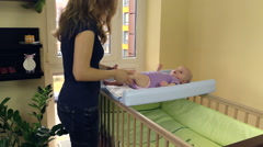 Mother make therapeutical massage for child lie on swaddle board Stock Footage