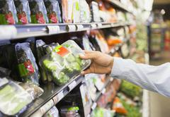 Close up of man holding produce in grocery store Stock Photos