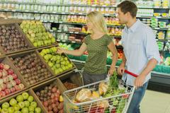 Couple shopping together in produce section of grocery store Stock Photos