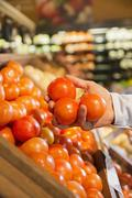 Close up of woman holding fruit in produce section of grocery store Stock Photos