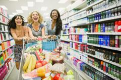 Women playing with shopping cart in grocery store aisle - stock photo