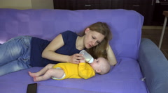 Mom and baby lie on couch, feed milk bottle. Kid care motherhood. 4K Stock Footage