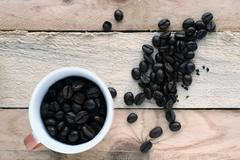 A cup of coffee and some scattered coffee beans - stock photo