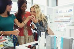 Women smelling perfume in drugstore Stock Photos