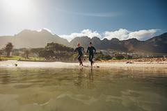 Two triathletes running into the water - stock photo