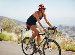 Female athlete riding cycle on country road Stock Photos