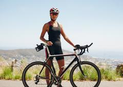 Confident female cyclist standing with her bicycle - stock photo