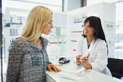 Woman discussing product with pharmacist in drugstore Stock Photos
