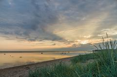 Calm and colourful cloudscape sunrise at sea gulf with tall grass on beach - stock photo