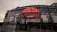 Famous Wrigley Field Ernie Banks Statue in front of Cubs Sign in the Rain Stock Footage