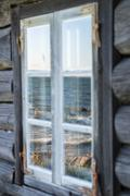 Seashore reflection in rustic cottage window of old wooden piscatorial house Stock Photos