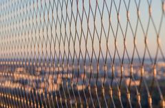 Metal mesh wire fence closeup on sunset light Stock Photos
