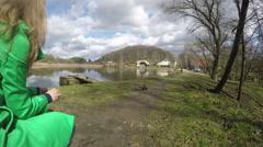 Blond woman in green coat feed duck birds near lake. 4K Stock Footage