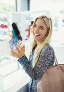 Woman trying on perfume in drugstore Stock Photos