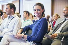 Portrait of smiling young woman sitting in audience in conference room Stock Photos