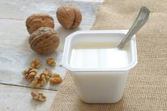 Stock Photo of Plain yogurt on a sack cloth with some nuts served in a table