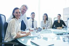 Three businesswomen and two businessmen sitting at conference table, smiling Stock Photos