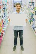 Man holding blank card in grocery store aisle - stock photo