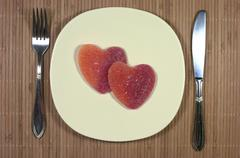 Knife, fork, heart shaped sugar sweets, plate. - stock photo