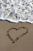 Heart in the sand, beach, water. - stock photo