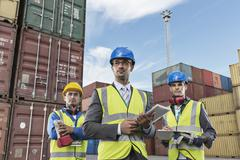 Businessmen wearing protective workwear near cargo containers Stock Photos