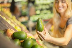 Close up of woman holding produce in grocery store Stock Photos