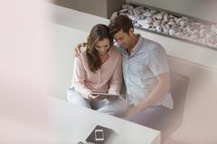 Stock Photo of Couple using tablet pc in dining room