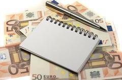 Notepad, pencil and banknotes - stock photo