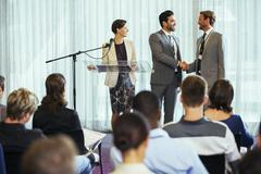 Businessmen shaking hands during presentation in conference room, businesswoman Kuvituskuvat